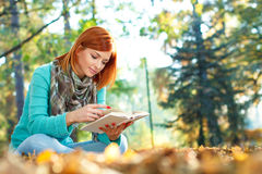 Young woman reading a book in park Stock Photos