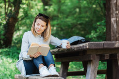 Young woman reading a book. In the park Stock Photos