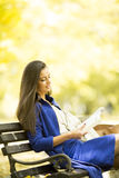 Young woman reading a book in the park. Woman reading a book in the park in autumn Stock Images