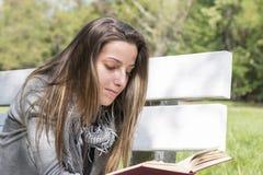Young woman reading a book on a park bench Stock Photos