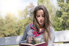 Young woman reading a book on a park bench Stock Photo