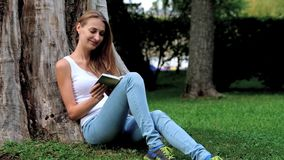 Young woman reading a book in the park stock footage