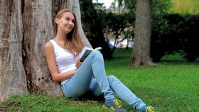Young woman reading a book in the park stock video