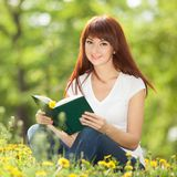 Young woman reading a book in the park with flowers. Royalty Free Stock Images