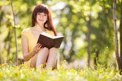 Young woman reading a book in the park with flowers Stock Image