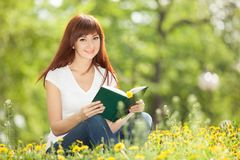 Young woman reading a book in the park with flowers Stock Photos