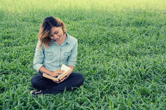 Young woman reading a book in the park on grass. Stock Image