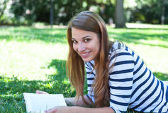 Young woman reading a book in a park Stock Images