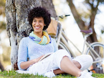 Young woman reading a book in park Stock Photography
