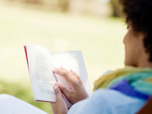 Young woman reading a book in park Stock Images