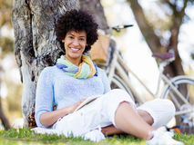 Young woman reading a book in park Royalty Free Stock Photo