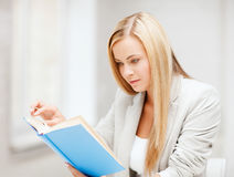 Young woman reading book at school Royalty Free Stock Photos