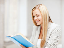 Young woman reading book at school Royalty Free Stock Photo