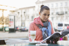 Young woman reading book at sidewalk cafe Stock Images