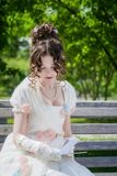 Young woman is reading a book sitting on a bench. Stock Photo
