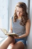 Young woman is reading the book Royalty Free Stock Images