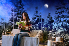 Young woman reading a book while sitting on a swing with a blank Royalty Free Stock Photography