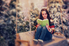 Young woman reading a book while sitting on a swing with her leg Stock Photography
