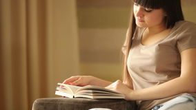 Young woman reading a book and smiling stock video