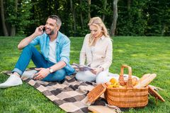 Young woman reading book and smiling man talking by smartphone while sitting together on plaid at picnic. In park royalty free stock photo