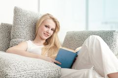 Young Woman Reading the Book on Sofa Stock Photo