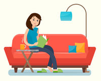 Young woman reading book on sofa at home. Stock Images