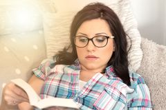 Young woman reading a book on sofa, light effect Royalty Free Stock Images