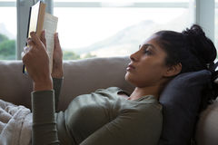 Young woman reading book on sofa Stock Image