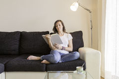 Young woman reading a book on a sofa Stock Images