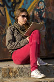 Young woman reading a book. On stairs in front of graffiti wall Stock Image