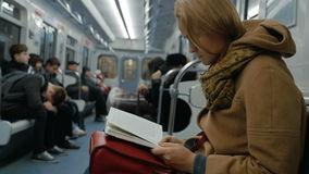 Young woman reading a book in subway. Slow motion of a young woman commuter reading a book in moving metro train. Passing the time during everyday ride stock video