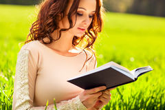 Young woman reading book. At summer field Stock Photos