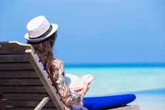 Young woman reading book on summer vacation at Stock Image