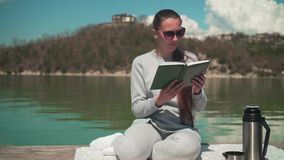 A young woman is reading a book in the sun, sitting on a wooden pier of a lake on a spring day, relaxing in nature. stock footage