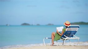 Young woman reading book on sunbeds during tropical white beach. Young woman reading book during tropical white beach stock video