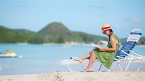 Young woman reading book on sunbeds during tropical white beach. Young woman reading book during tropical white beach stock video footage