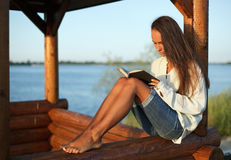 Young woman reading book on sunset. Young woman reading book in summerhouse on sunset stock photo