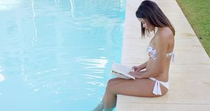 Young woman reading a book at the swimming pool stock video