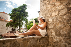 Young woman reading book on tablet on street at sunny day Royalty Free Stock Photography