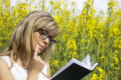 Young woman reading a book and thinking on the rape meadow Royalty Free Stock Images
