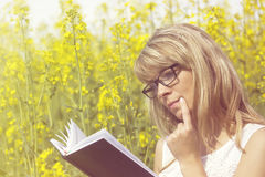 Young woman reading a book and thinking on the rape meadow Stock Image