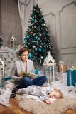 Young woman reading book to son at Christmas tree Stock Photos