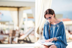 Young woman reading book during tropical beach vacation. Fashion girl read sitting in white sunbeds at european beach Royalty Free Stock Photo