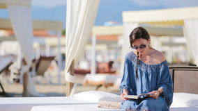Young woman reading book during tropical beach vacation. Fashion girl read sitting in white sunbeds at european beach stock video footage