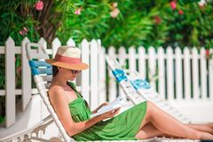 Young woman reading book on chaise-lounge on the beach. Young woman reading book during tropical white beach stock images