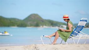 Young woman reading book on sunbeds on tropical white beach. Young woman reading book during tropical white beach stock video footage