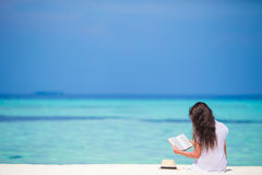 Young woman reading book during tropical white Stock Image