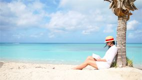Young woman reading book on white beach sitting under the palmtree. Young woman reading book during tropical white beach stock video
