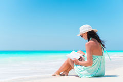 Young woman reading book on white sand beach. Young woman reading book during tropical white beach royalty free stock photography