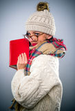 Young woman reading a book in winter outfit Stock Photos